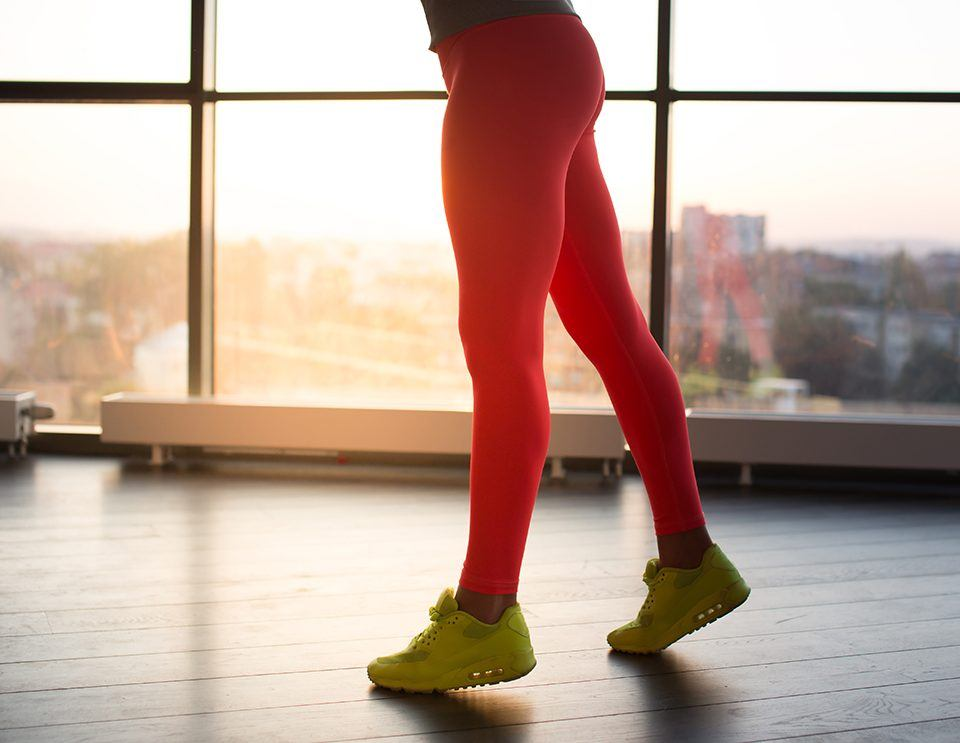 Woman's legs in red sports pants and yellow shoes.